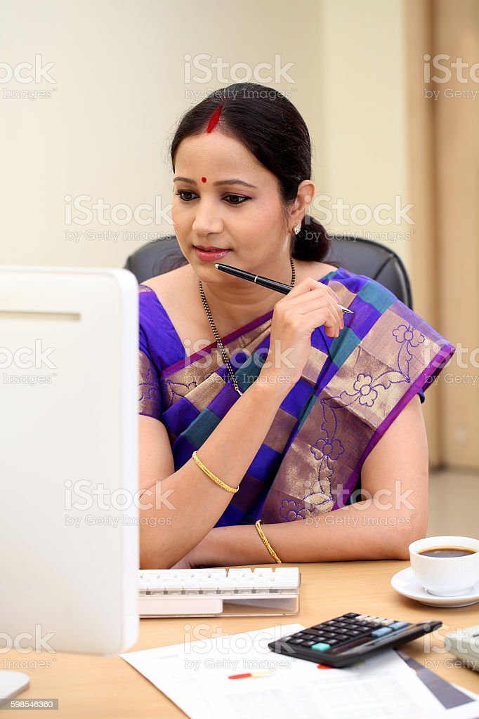 Happy traditional Indian business woman at office desk stock photo