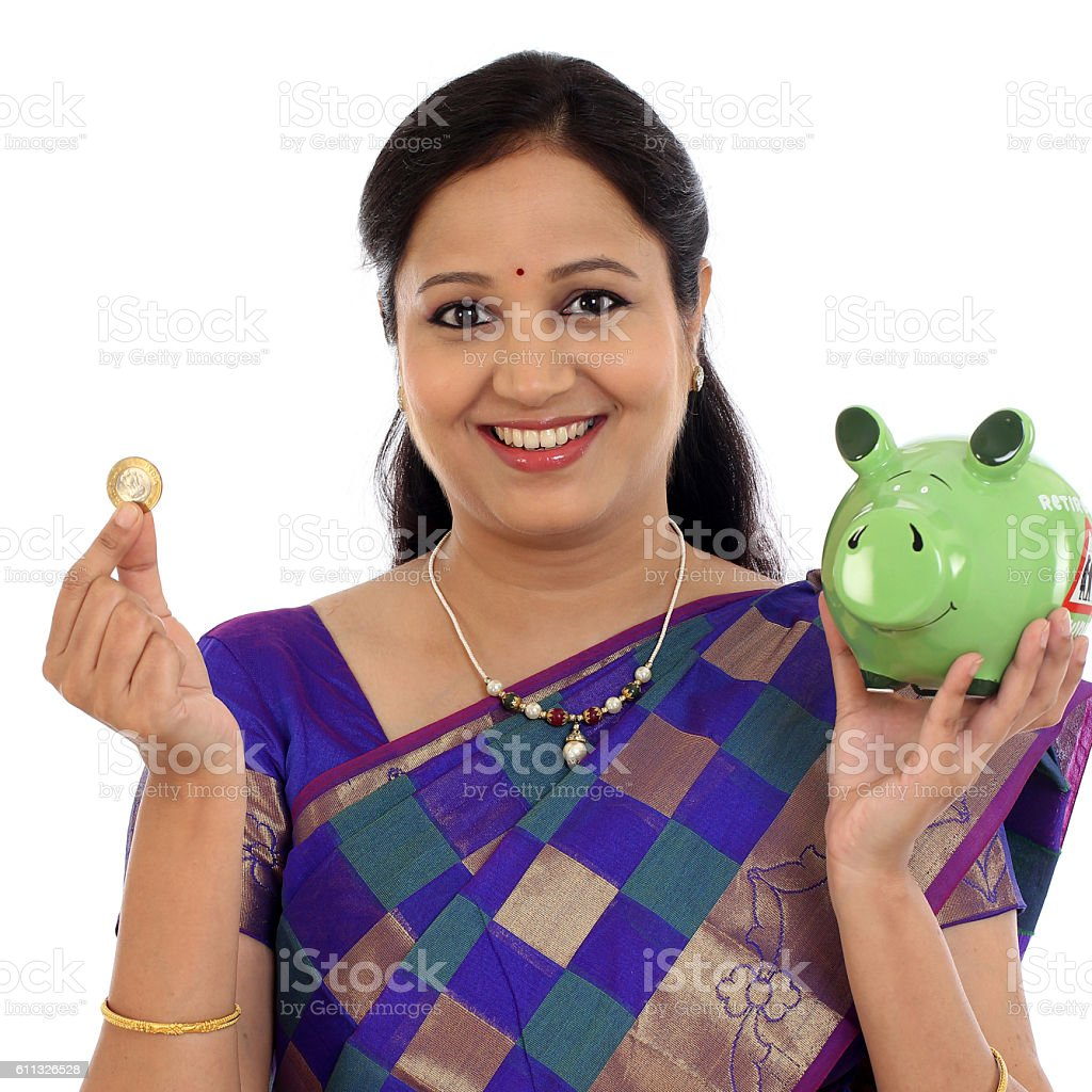 Happy traditional Indian woman holding a piggy bank stock photo