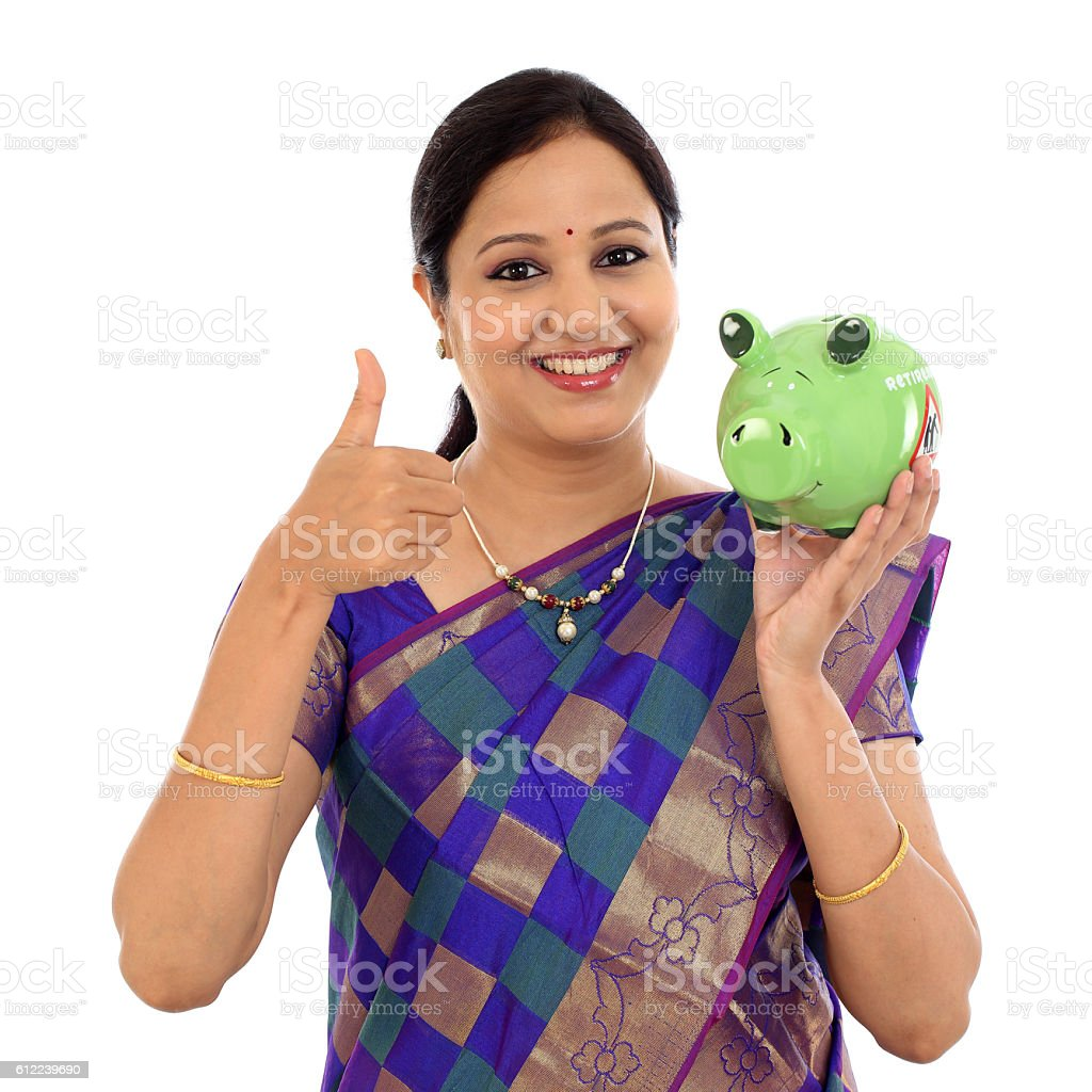 Happy traditional woman holding piggy bank stock photo
