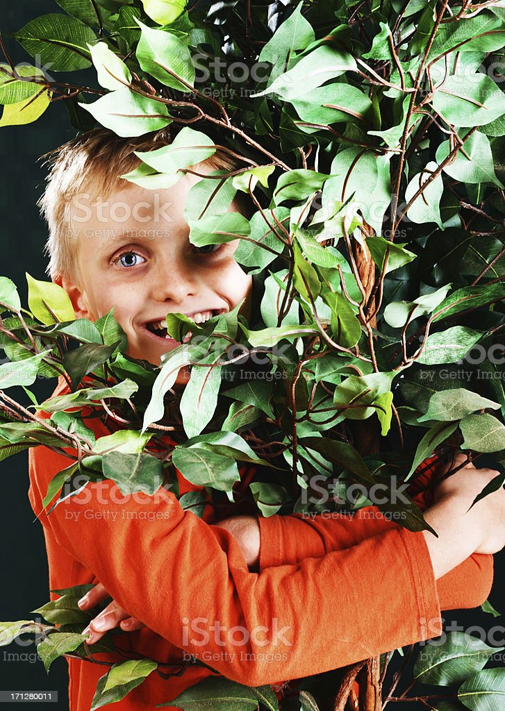 Happy tree-hugging little boy cares for the environment stock photo