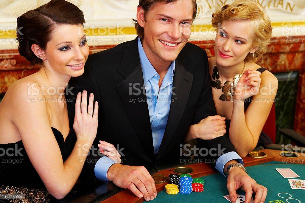 Happy trio gambling at the casino royalty-free stock photo