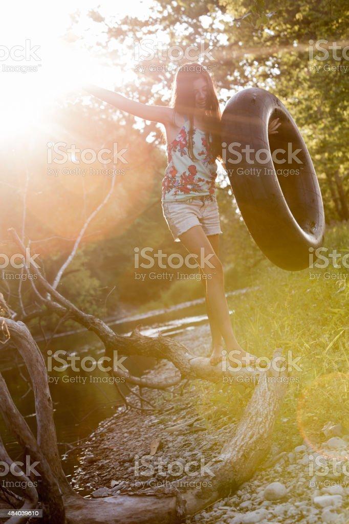 Happy Tween girl balance walking on Tree stock photo