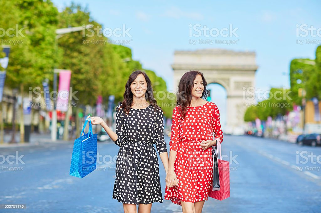 Happy twin sisters doing shopping on holidays in France stock photo