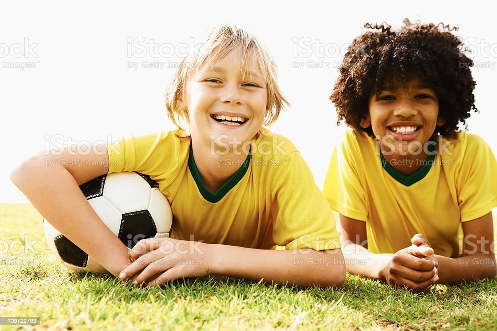 Happy two football players lying on the field royalty-free stock photo