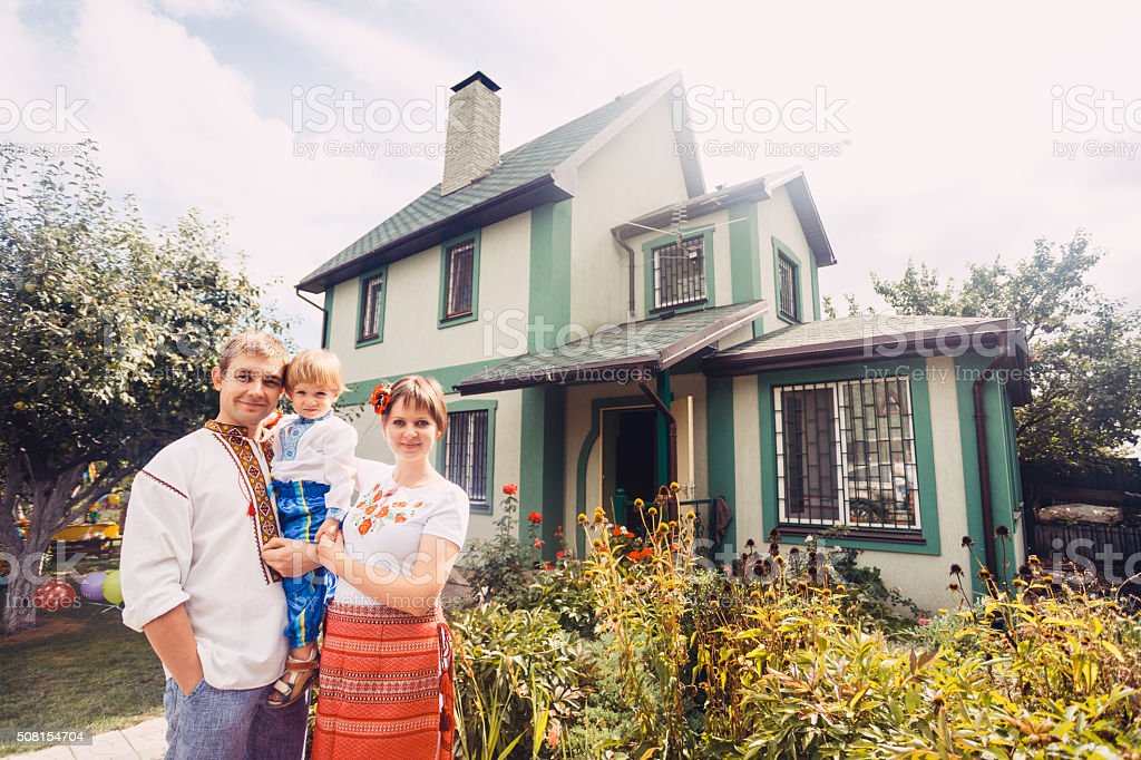Happy Ukrainian family dressed in ethnic costumes and house stock photo