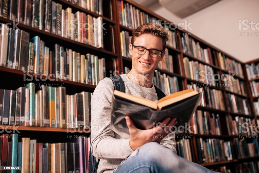 Happy university student studying in library stock photo