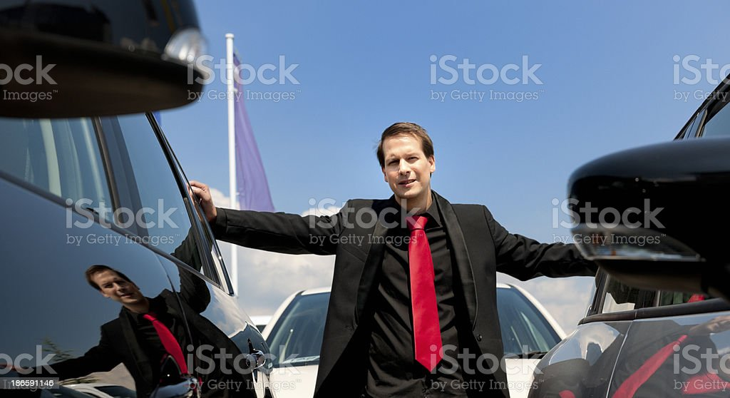 happy used car salesman in parking lot royalty-free stock photo
