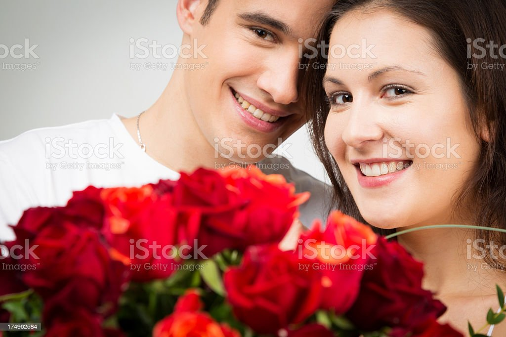 happy valentine's couple holding bouquet of roses stock photo