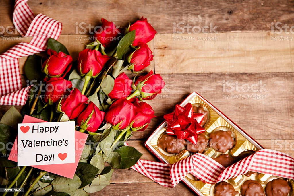 Happy Valentine's Day. Red roses bouquet, chocolate candy, notecard, ribbon. stock photo