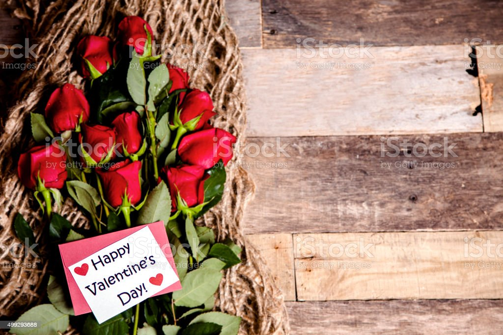 Happy Valentine's Day. Red roses bouquet, notecard, burlap. Rustic table. stock photo