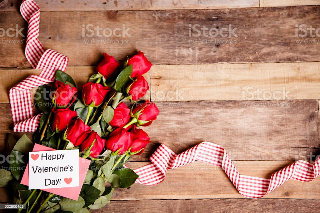 Happy Valentine's Day. Red roses bouquet, notecard, ribbon. Rustic table. stock photo