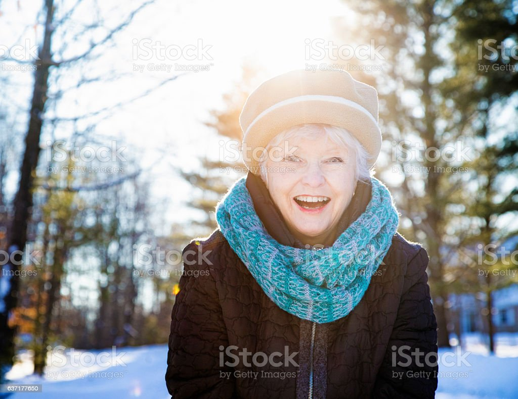 Happy vibrant senior woman portrait in wintry Canadian forest stock photo