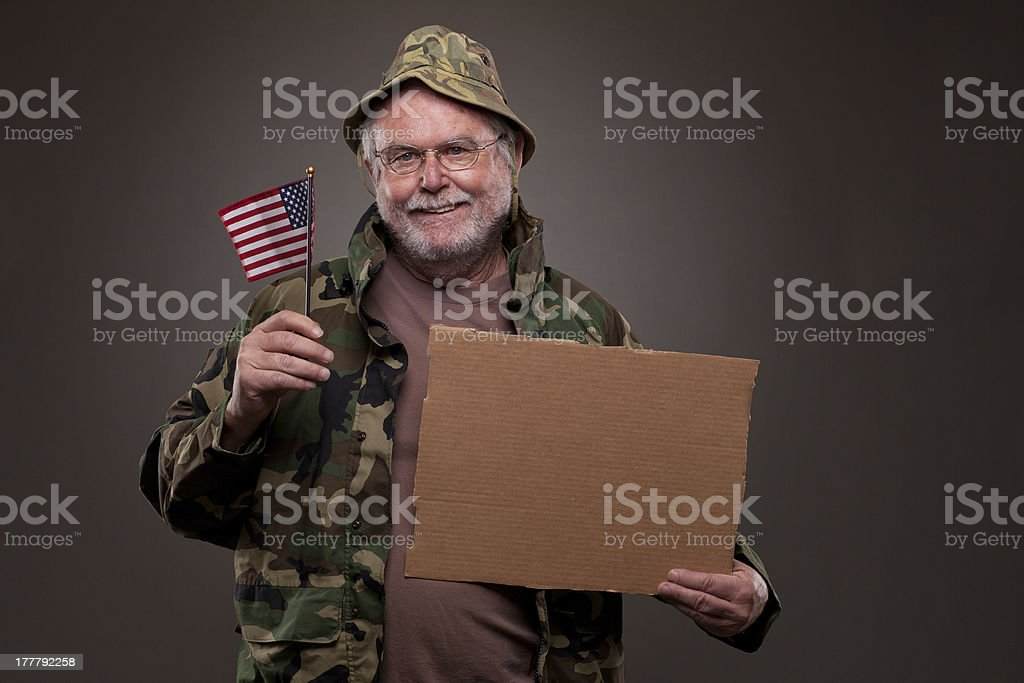 Happy Vietnam Veteran holding a cardboard piece and American fla royalty-free stock photo