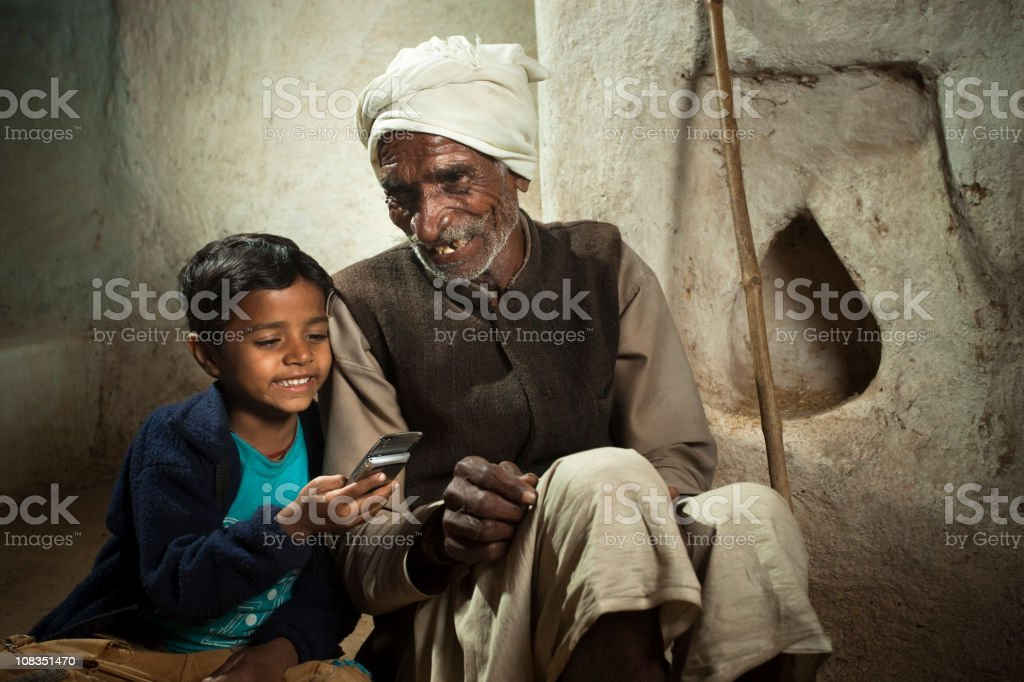 Happy village boy playing with his grandfather's mobile phone stock photo