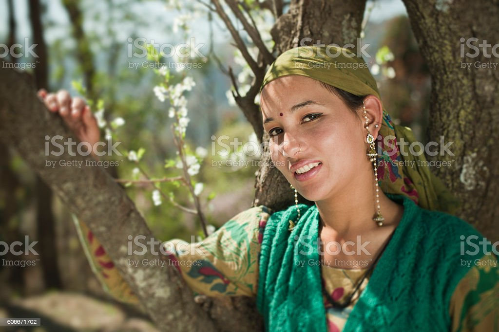 Happy village girl standing by holding tree, looking at camera. stock photo
