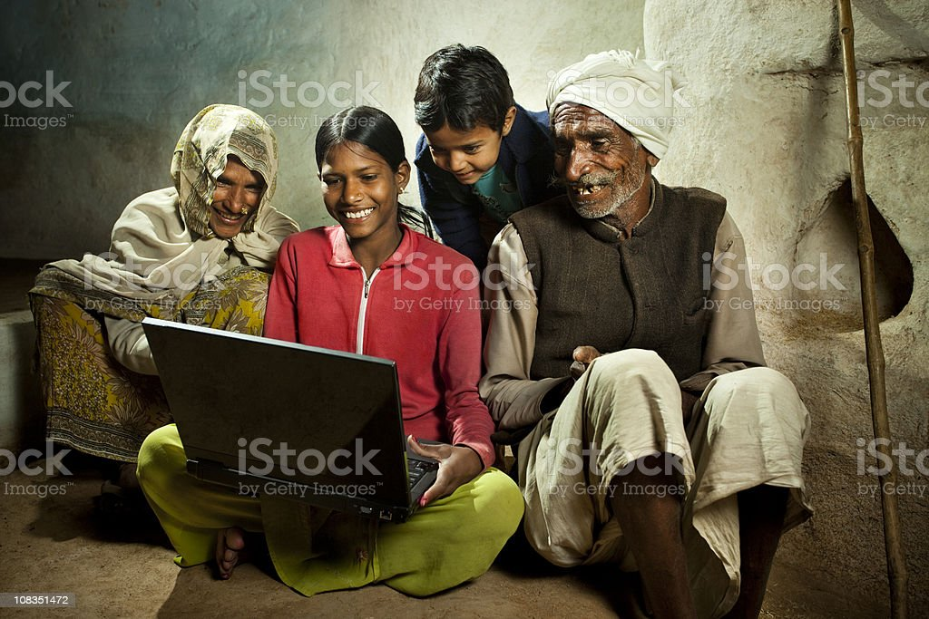 Happy village girl using laptop with mother, brother and grandfa royalty-free stock photo