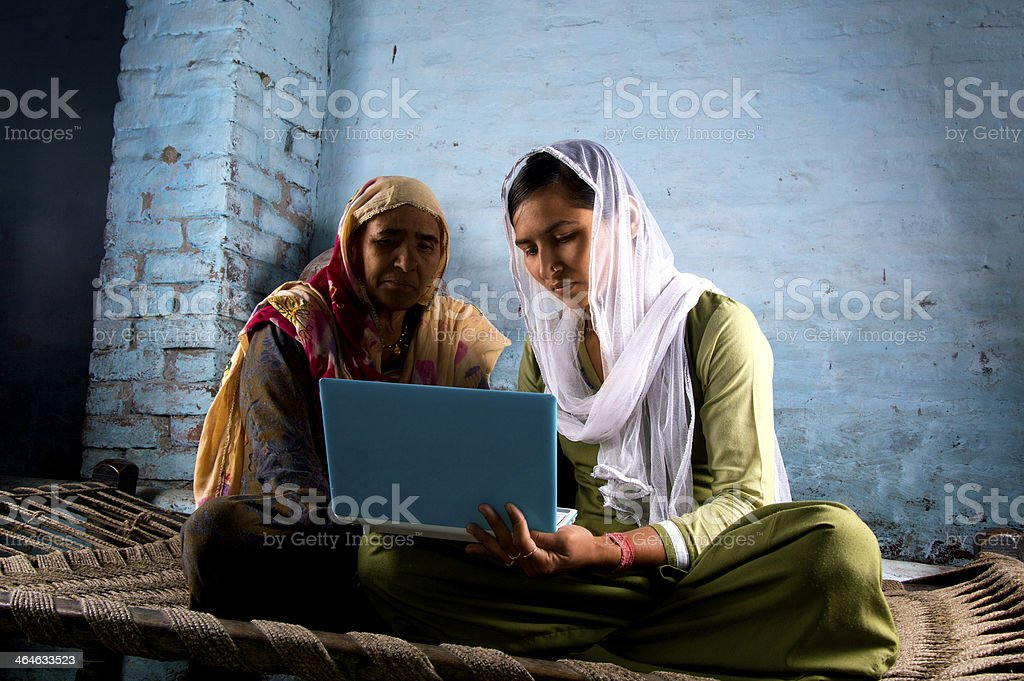 Happy villager girl using laptop with her mother royalty-free stock photo