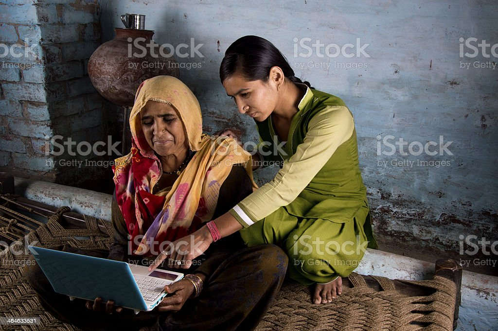 Happy villager girl using laptop with her mother stock photo