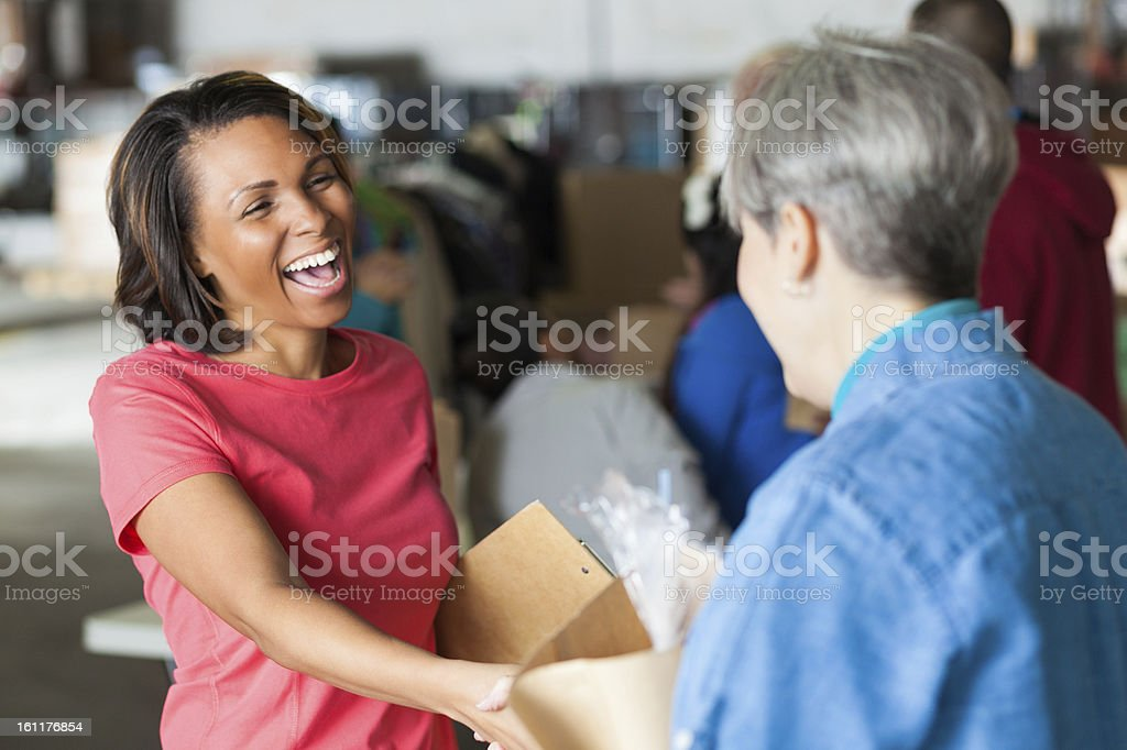 Happy volunteer accepting donations at food and clothing bank royalty-free stock photo