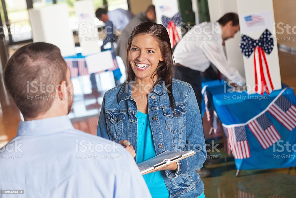 Happy volunteer asking exit poll questions at election voting center stock photo
