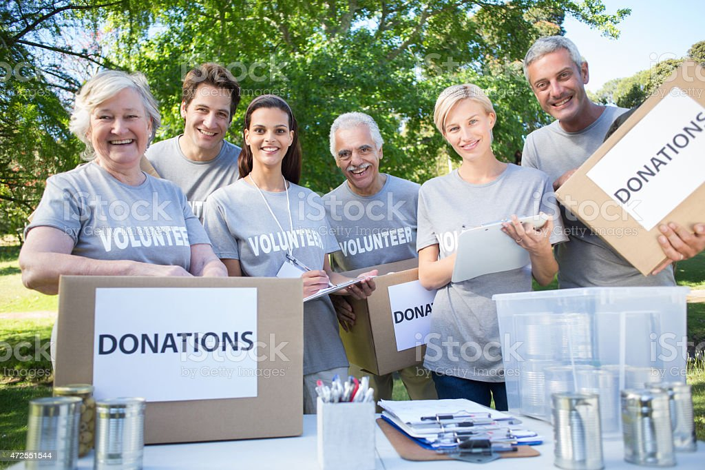 Happy volunteer family holding donation boxes stock photo