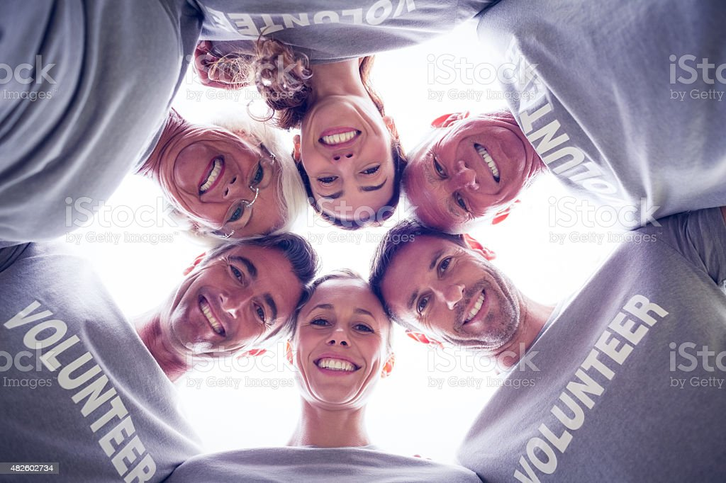 Happy volunteer family looking down at the camera stock photo