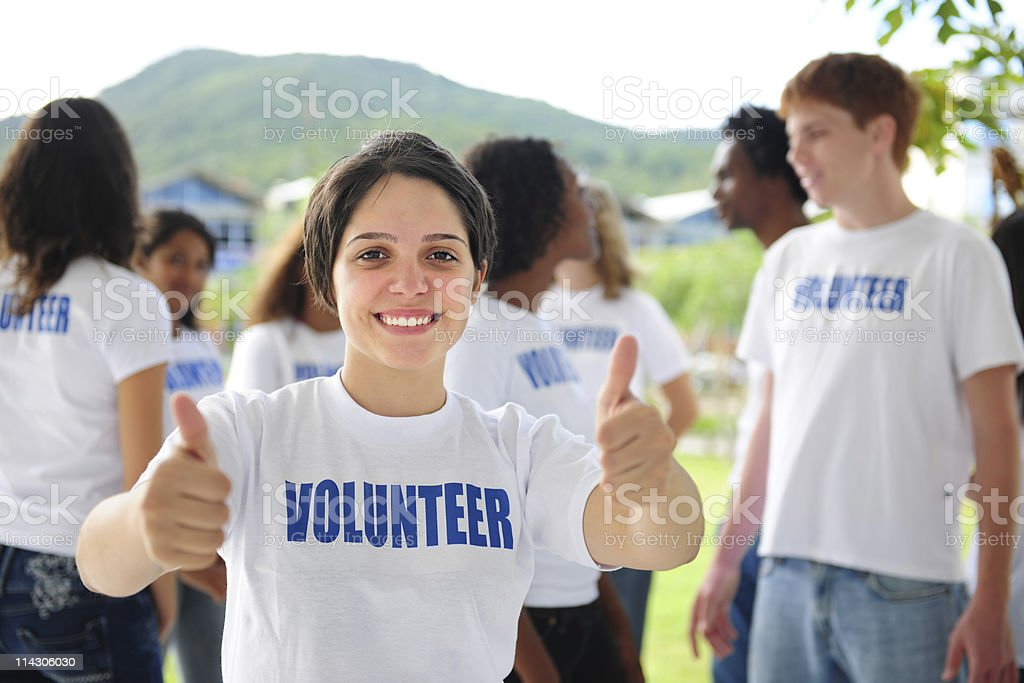 happy volunteer girl showing thumbs up sign stock photo