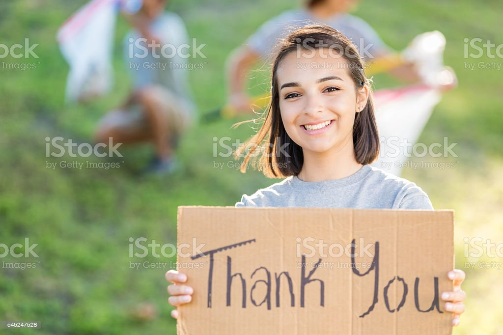 Happy volunteer holding up a cardboard sign that says \'Thank you\' on...