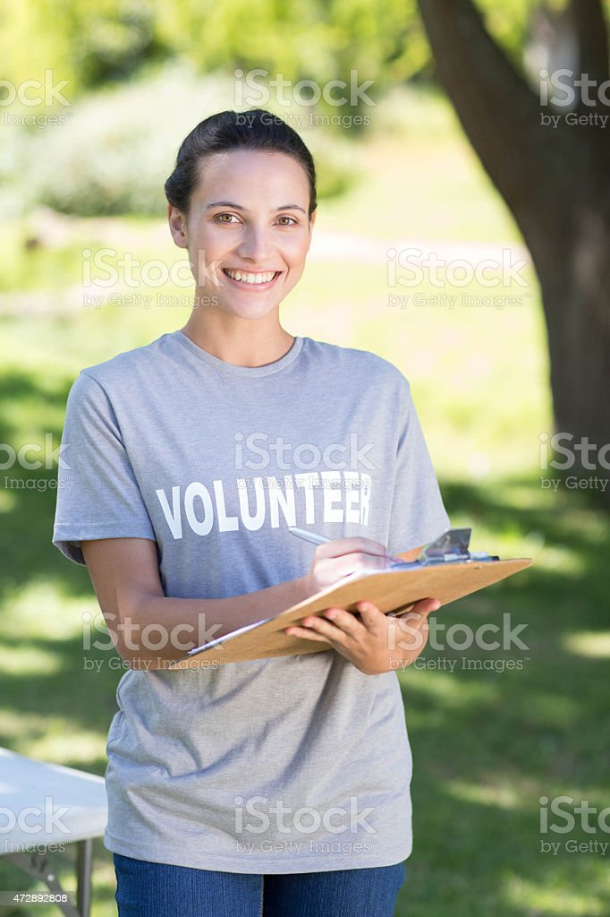 Happy volunteer in the park stock photo