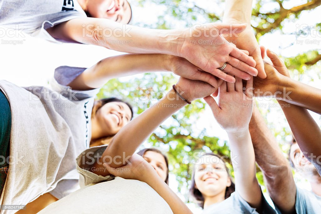 Happy volunteers putting their hands together in a powwow stock photo