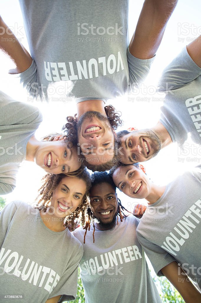 Happy volunteers smiling in the park stock photo
