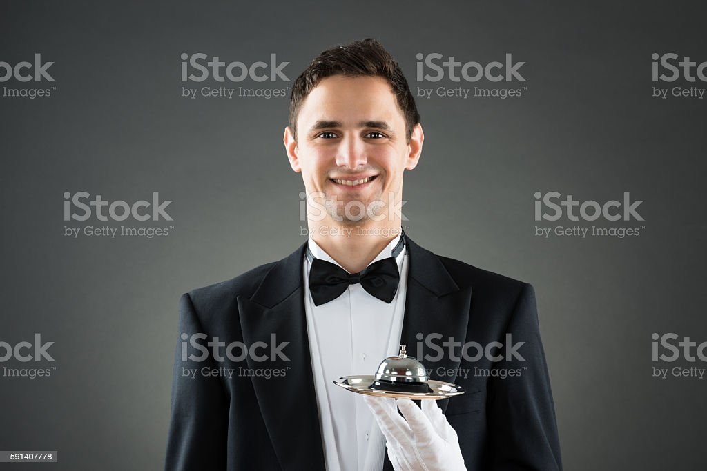 Happy Waiter Holding Service Bell In Plate stock photo