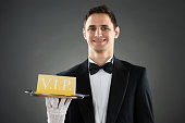Happy Waiter Holding Tray With VIP Sign