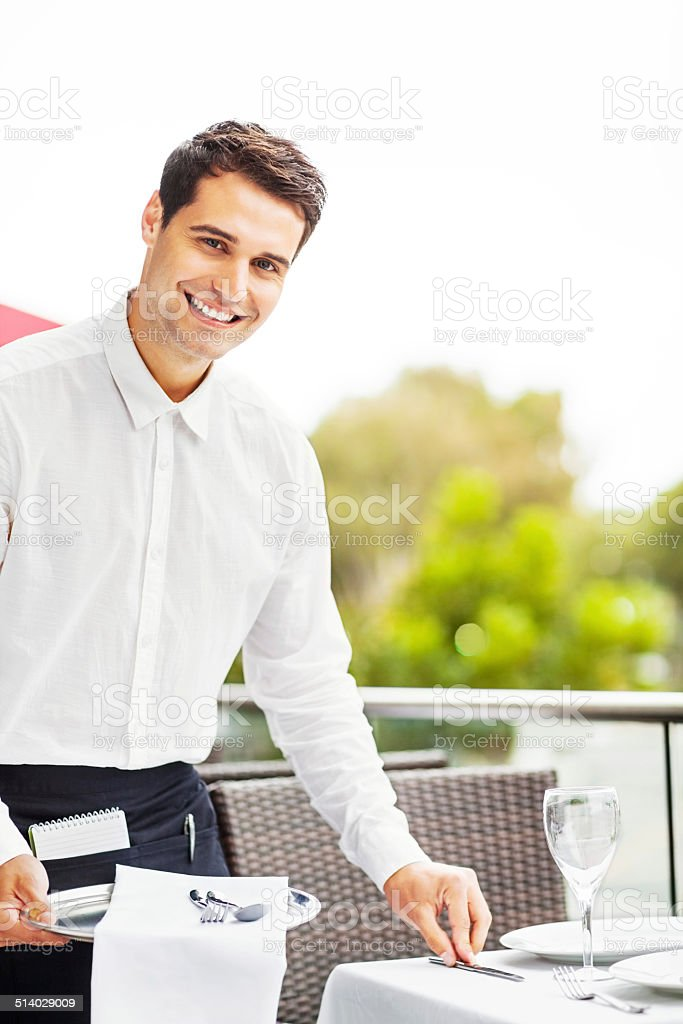 Happy Waiter Setting Table In Restaurant stock photo