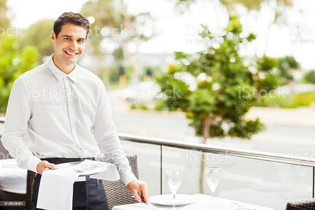 Happy Waiter Setting The Table In Restaurant stock photo