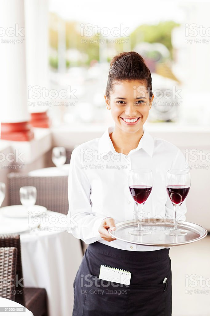 Happy Waitress Carrying Tray With Wine Glasses In Restaurant stock photo