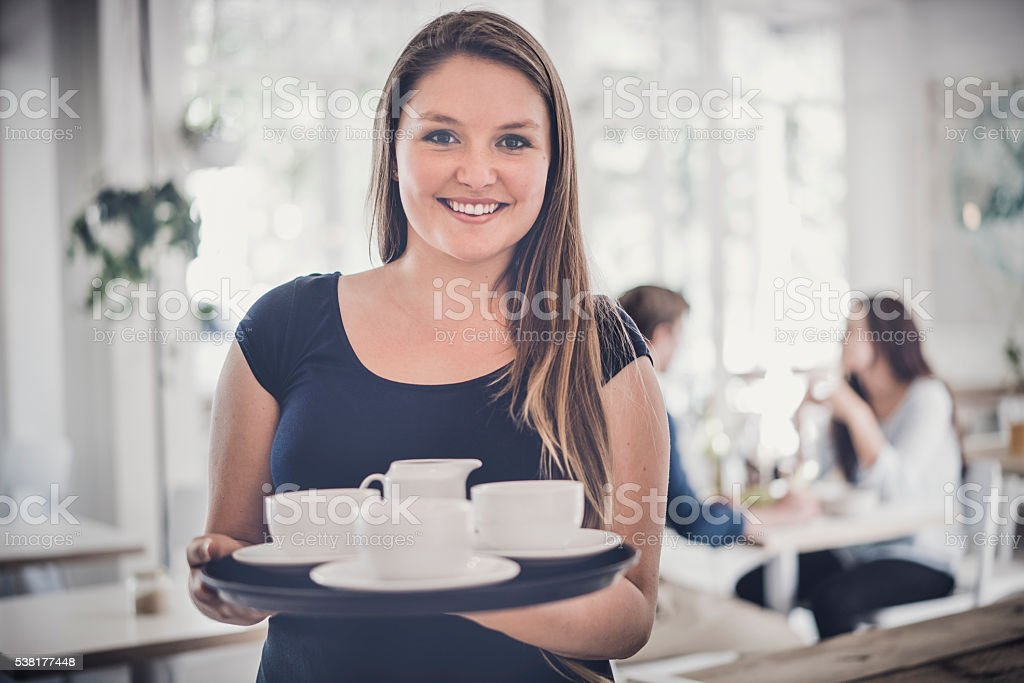 Happy waitress holding tray of coffee cups in cafe stock photo