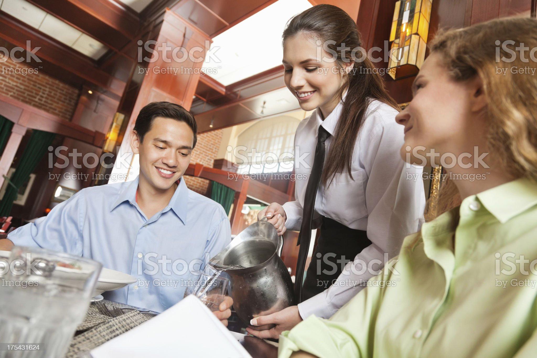 Happy waitress refilling drinks in nice restaurant royalty-free stock photo