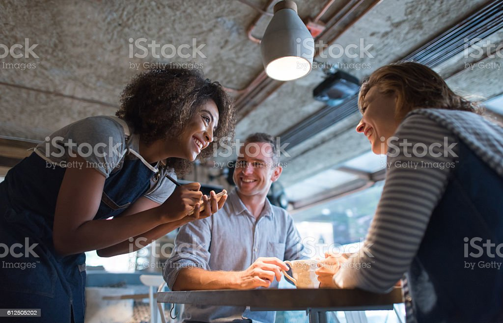 Happy waitress taking an order at a restaurant stock photo