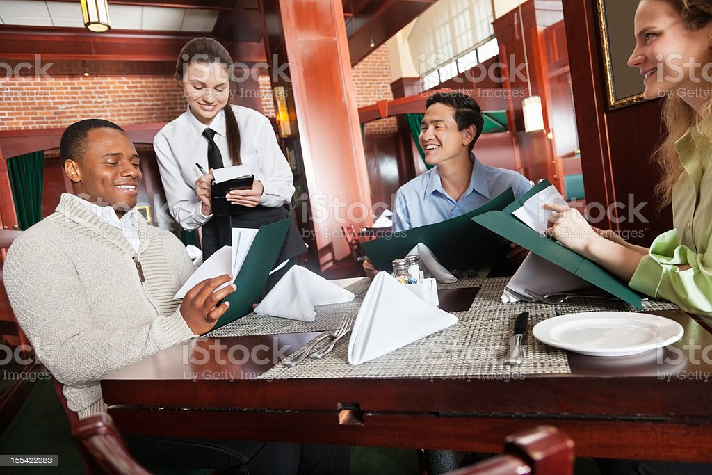 Happy waitress taking orders in nice restaurant stock photo