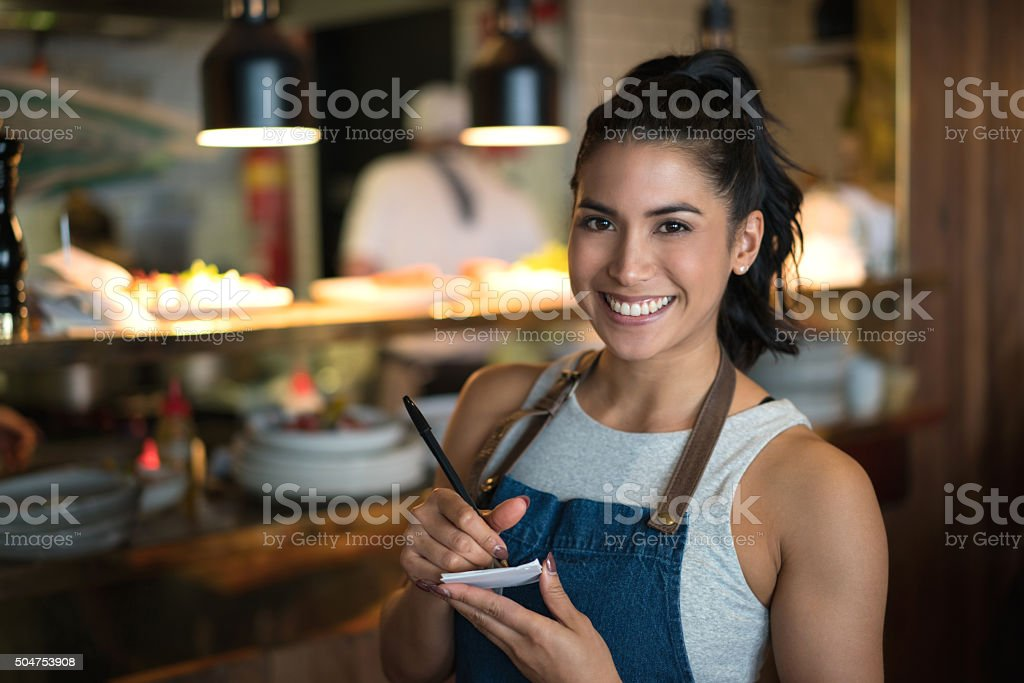 Happy waitress working at a coffee shop stock photo