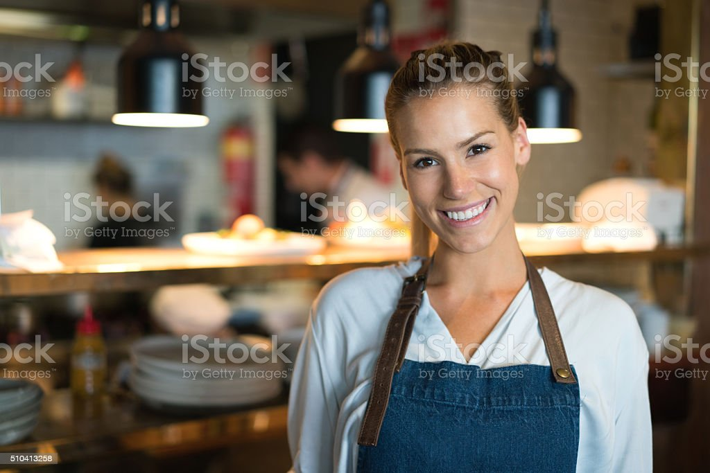 Happy waitress working at a restaurant stock photo