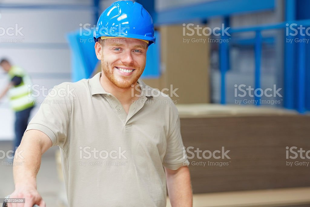 Happy warehouse worker wearing a hardhat stock photo
