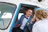Happy wedding couple bride and groom riding helicopter