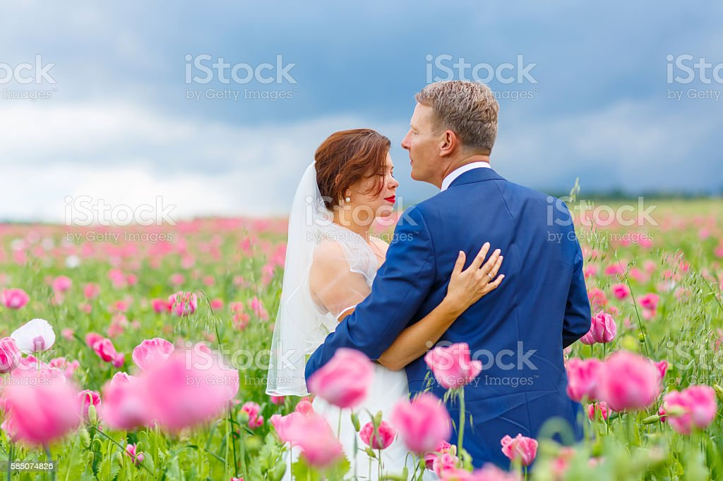 Happy wedding couple in pink poppy field stock photo
