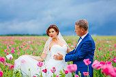 Happy wedding couple in pink poppy field