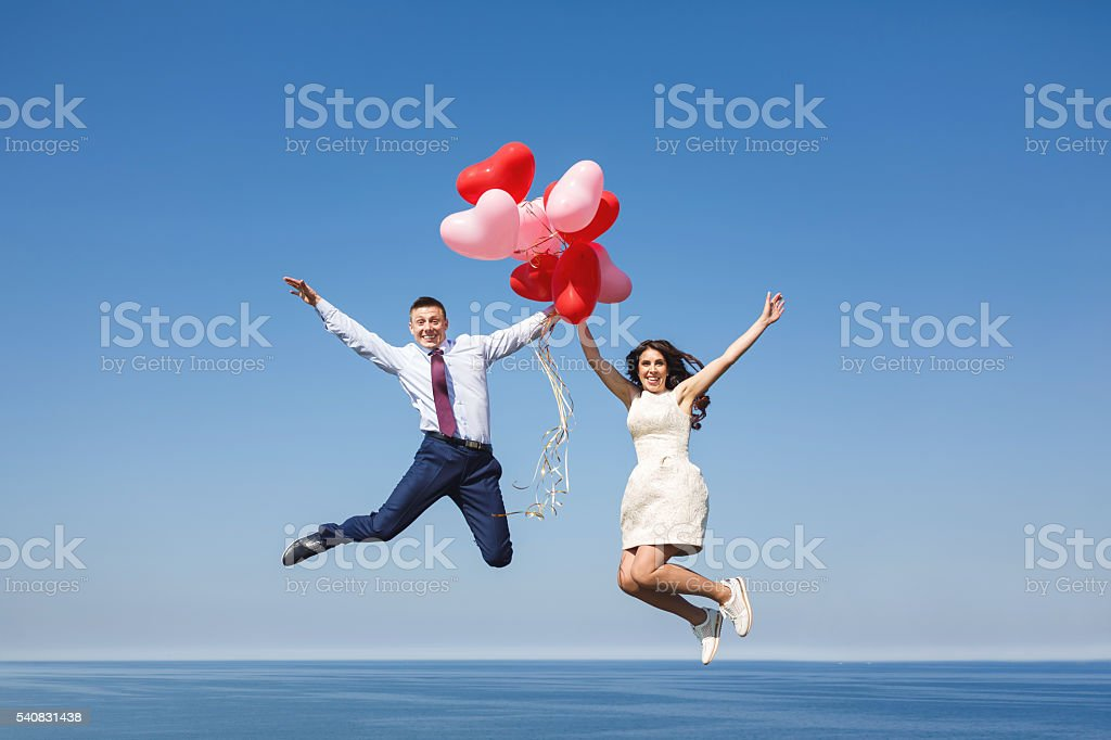 Happy wedding couple with red balloons stock photo