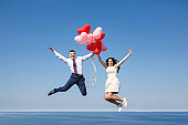 Happy wedding couple with red balloons