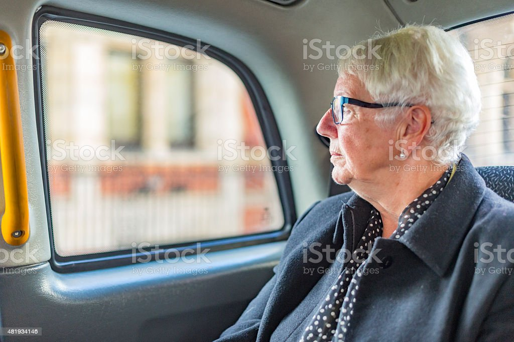 Happy Well Dressed Senior Woman In a London Taxi stock photo
