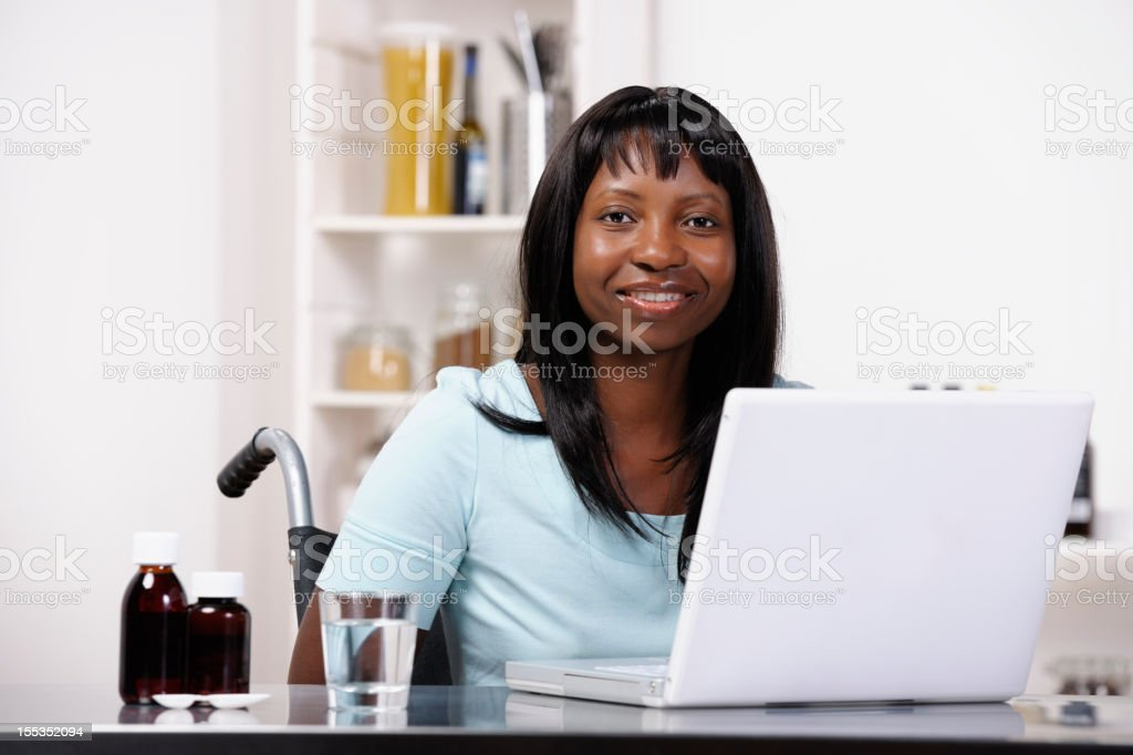 Happy Wheelchair Bound African American Woman Using Laptop stock photo